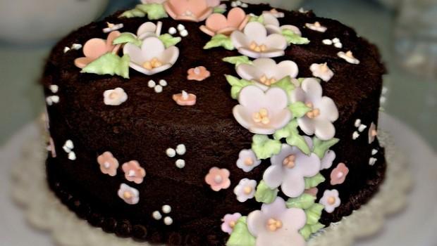 Torta al cioccolato decorata con fiori di pasta di zucchero