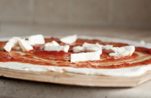 La pizza romana condita con pomodoro e mozzarella