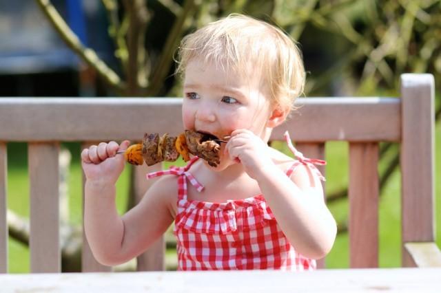 Bambina mangia uno spiedino