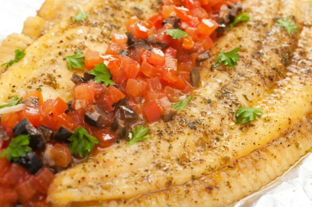 Grilled turbot with herbs and a tomato and olive salsa, close-up.