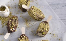 Vanilla ice cream sticks with a chocolate and pistachio coating