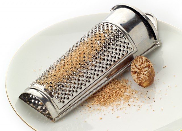 Nutmeg and grater on a plate, with freshly ground spice