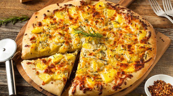 La pizza con patate e cipolle con la ricetta rustica