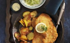Wiener Schnitzel (breaded veal escalope from Vienna) with fried potatoes and a cucumber salad