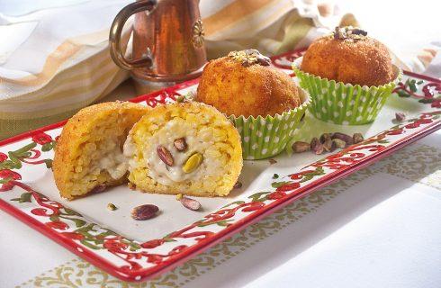 Arancine farcite con besciamella ai pistacchi, street food siciliano