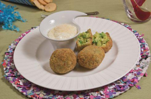 Arancini di riso allo zafferano con piselli, accompagnati da crema al parmigiano