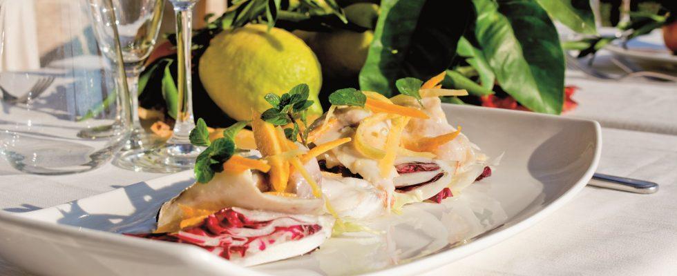 Carpaccio di spigola marinato agli agrumi con insalatina aromatica