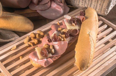 Panino con mortadella, pecorino, uva caramellata e anacardi croccanti, un piatto croccante e saporito
